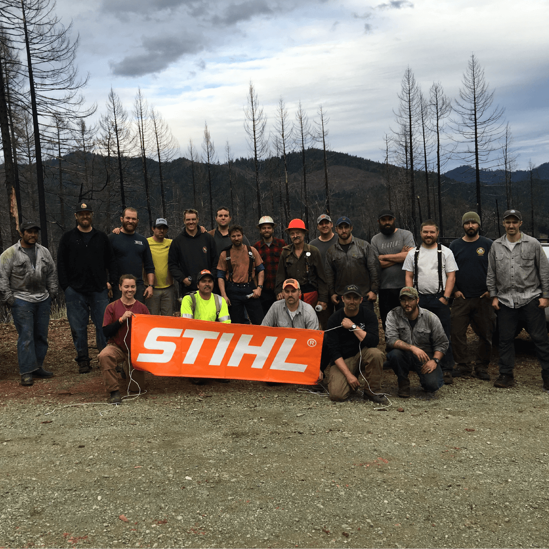 Group gathers for a photo after a fire-weakened tree workshop, holding STIHL sign.